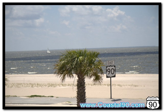 Sailboat from beach in Pass Christian on Highway 90. Sign, palm and Sailboat in one photo.